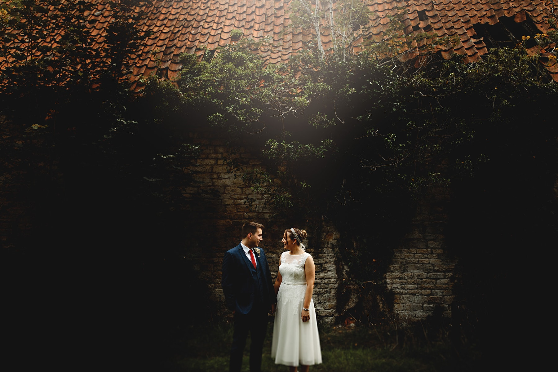 bride and groom stood by a wall on the blankney estate on their wedding day