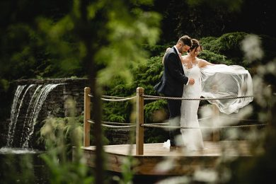 bride and groom stood in green gardens overlooking the pond at Redhouse barn wedding venue