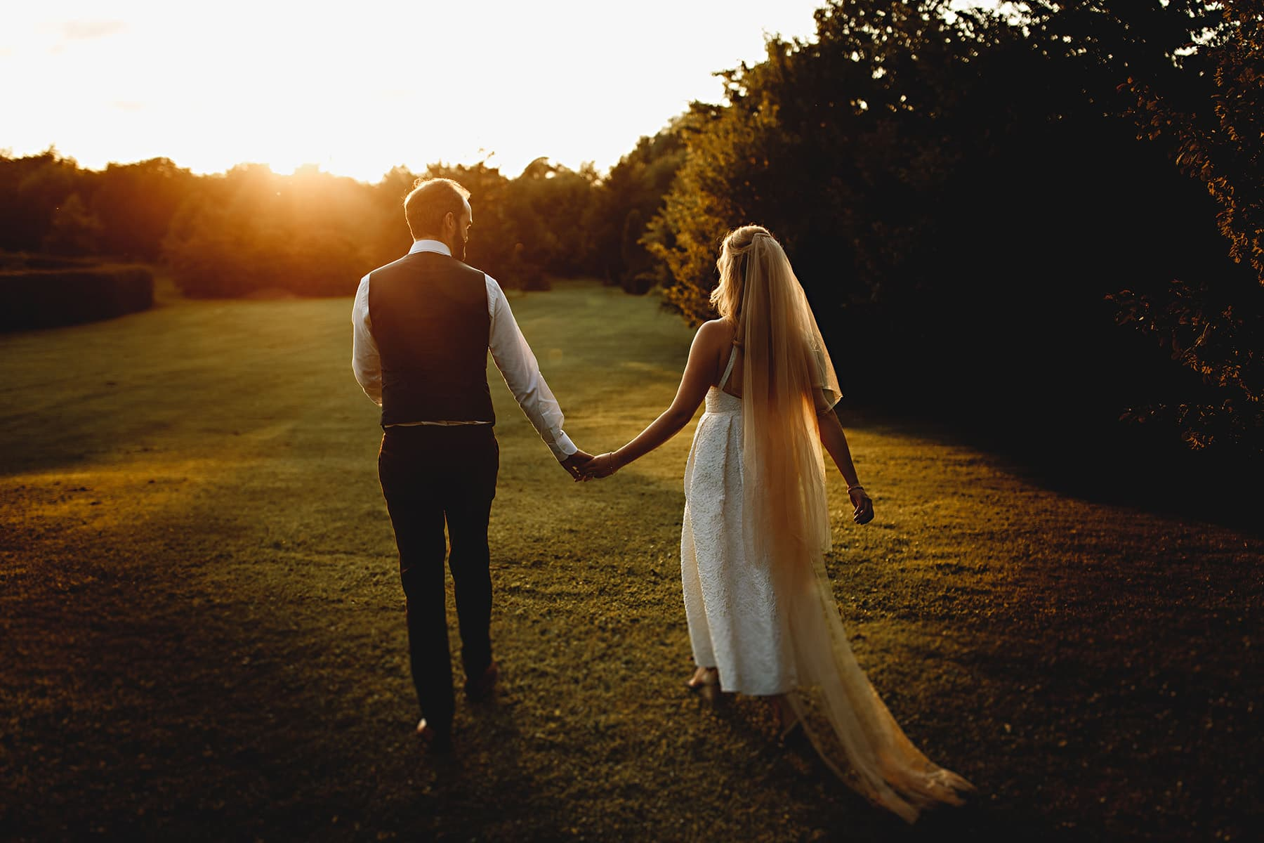 bride and groom walking away from the camera in golden orange sunlight on their wedding day