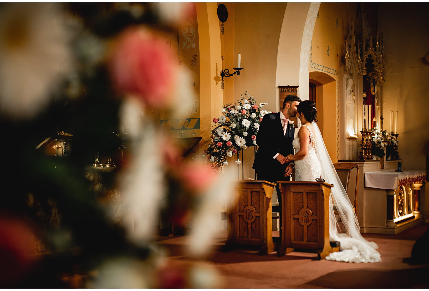 the bride and groom kissing in the church