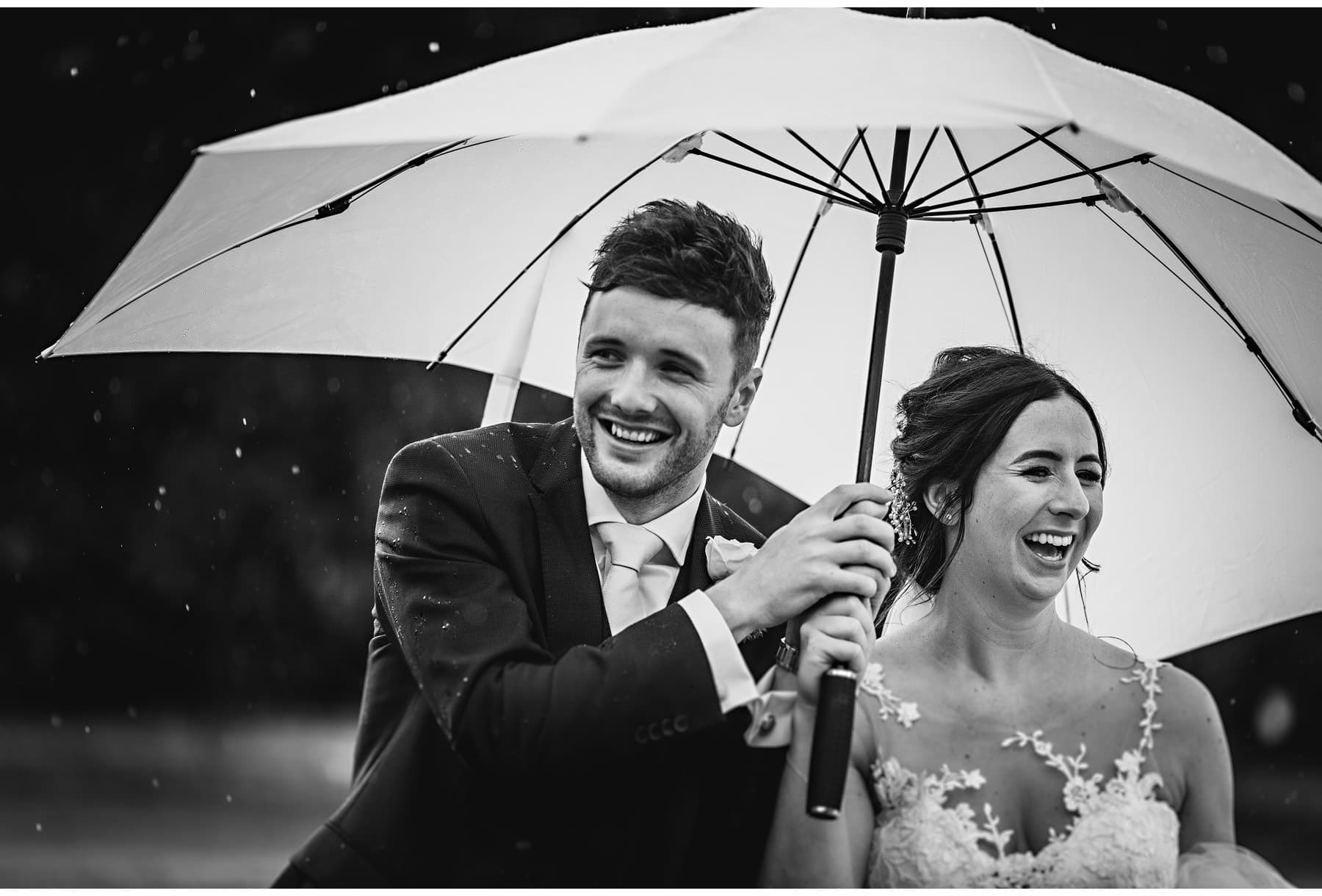 the bride & groom under an umbrella