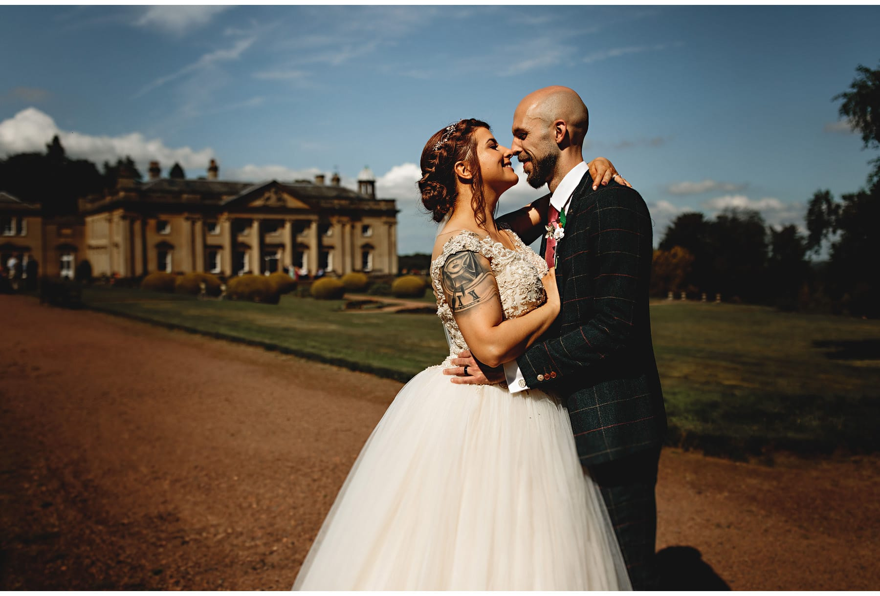 the bride and groom kissing with wortley hall in the background