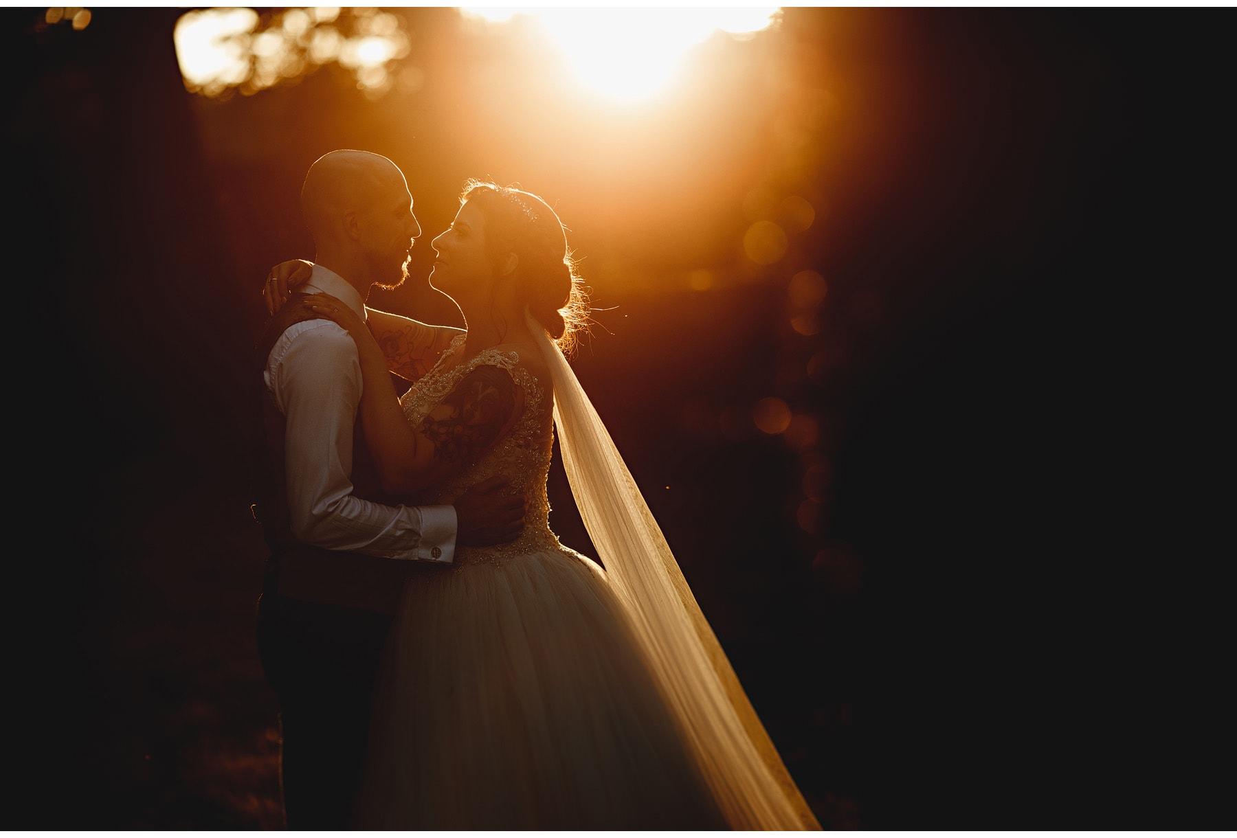 bride and groom in orange golden hour sunlight at wortley hall