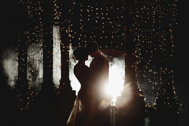 bride and groom at weston hall in orange twinkle lights in the dark