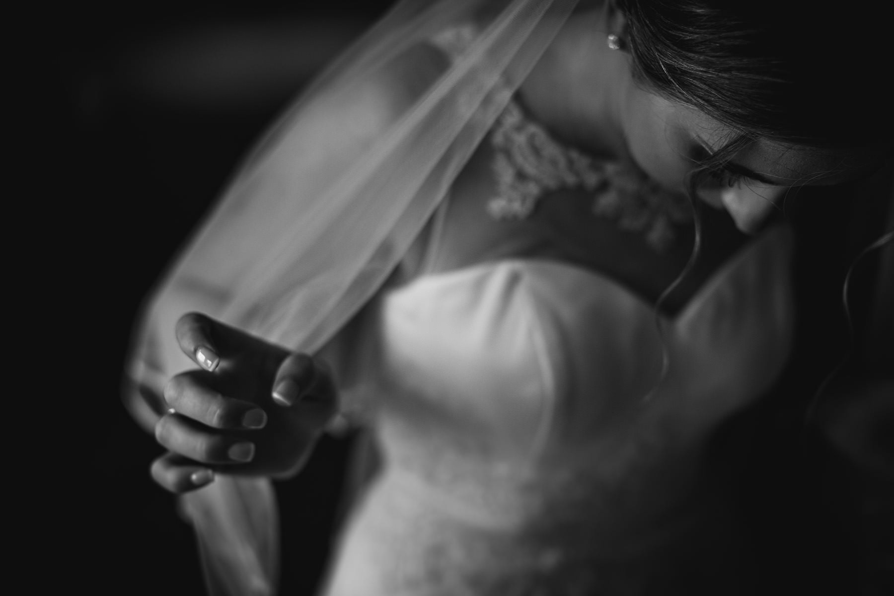 the bride putting on her wedding viel at Makeney Hall