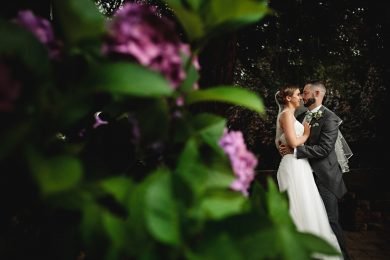 bride and groom surrounded by green plans on thier wedding day at Makeney Hall in Derbyshire