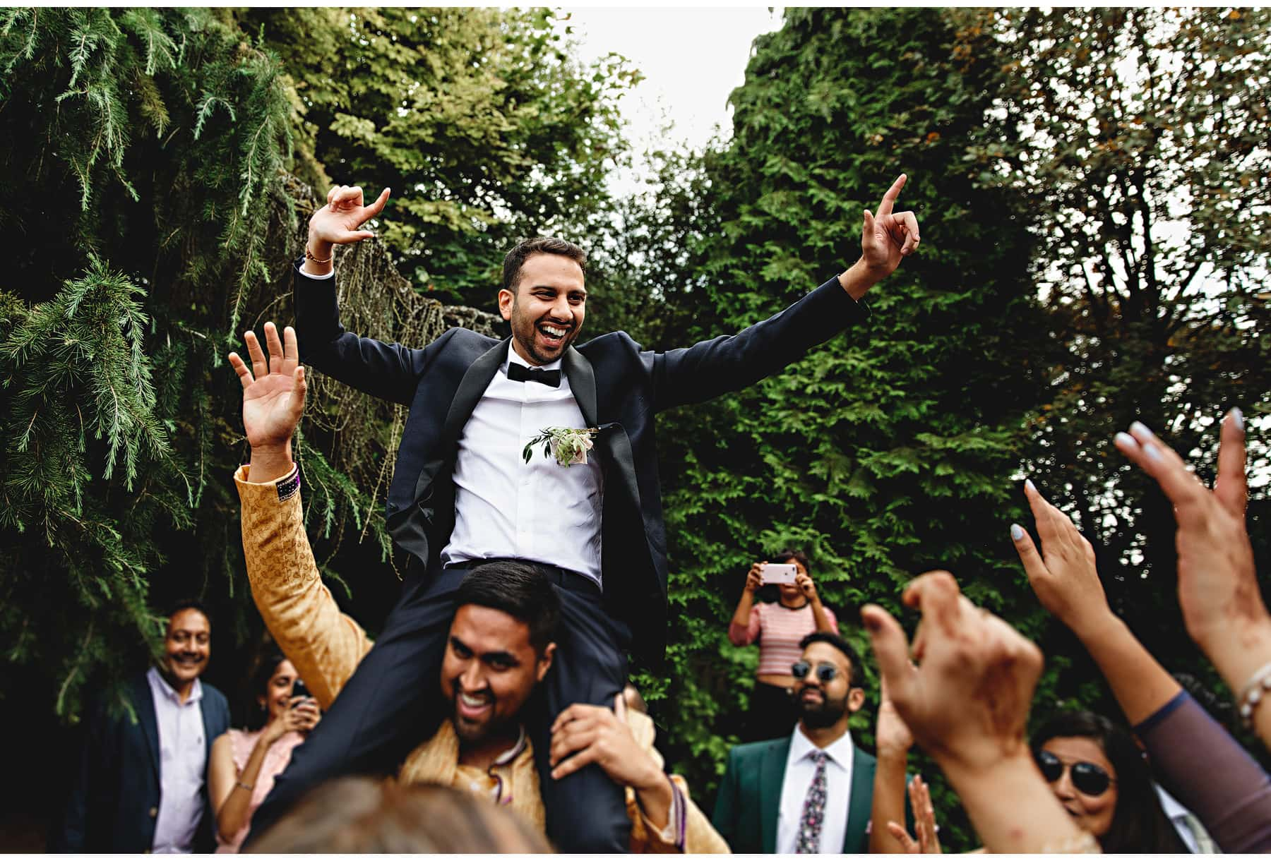 the groom on a guests shoulders