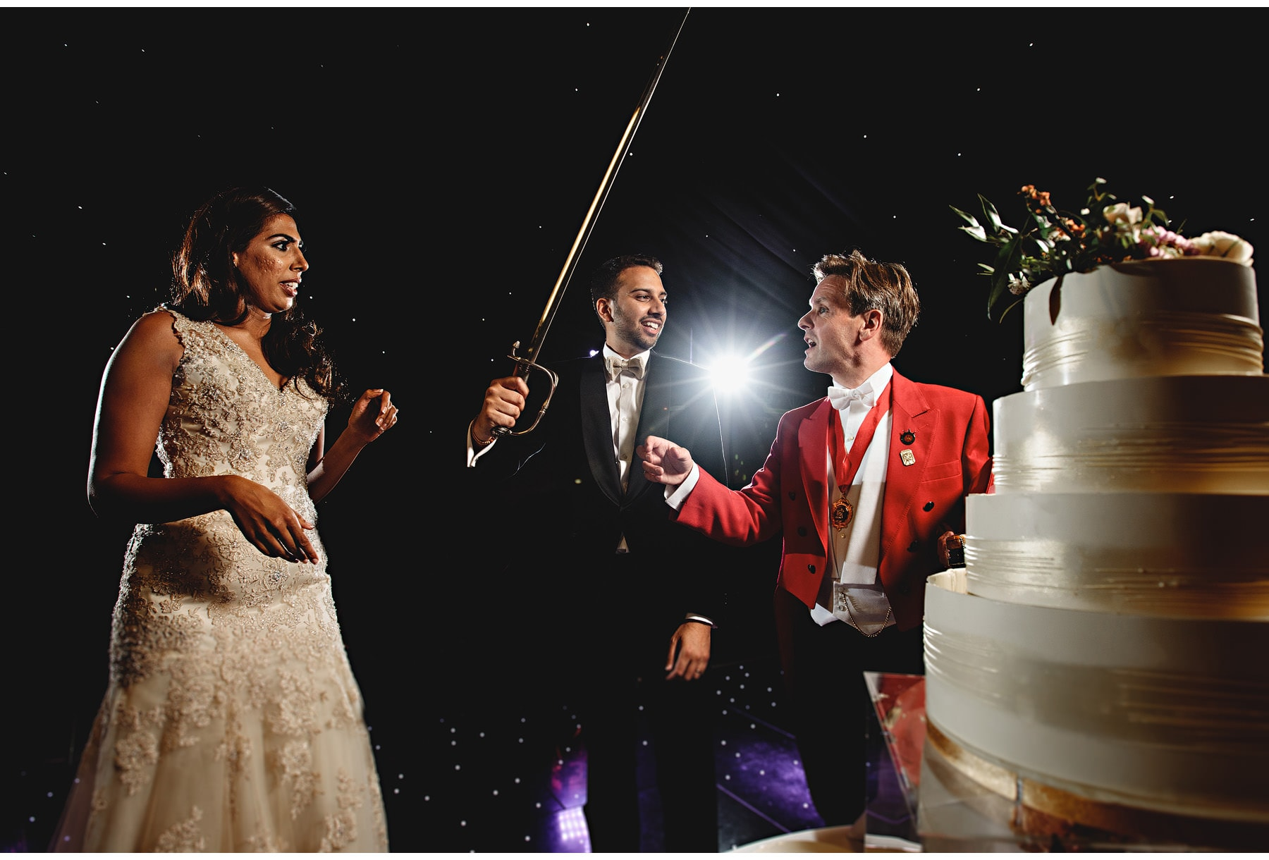 the bride & groom cut their cake with a sword