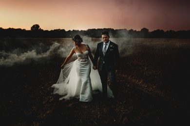 the bride and groo,m in misty fields at sunset on their wedding day