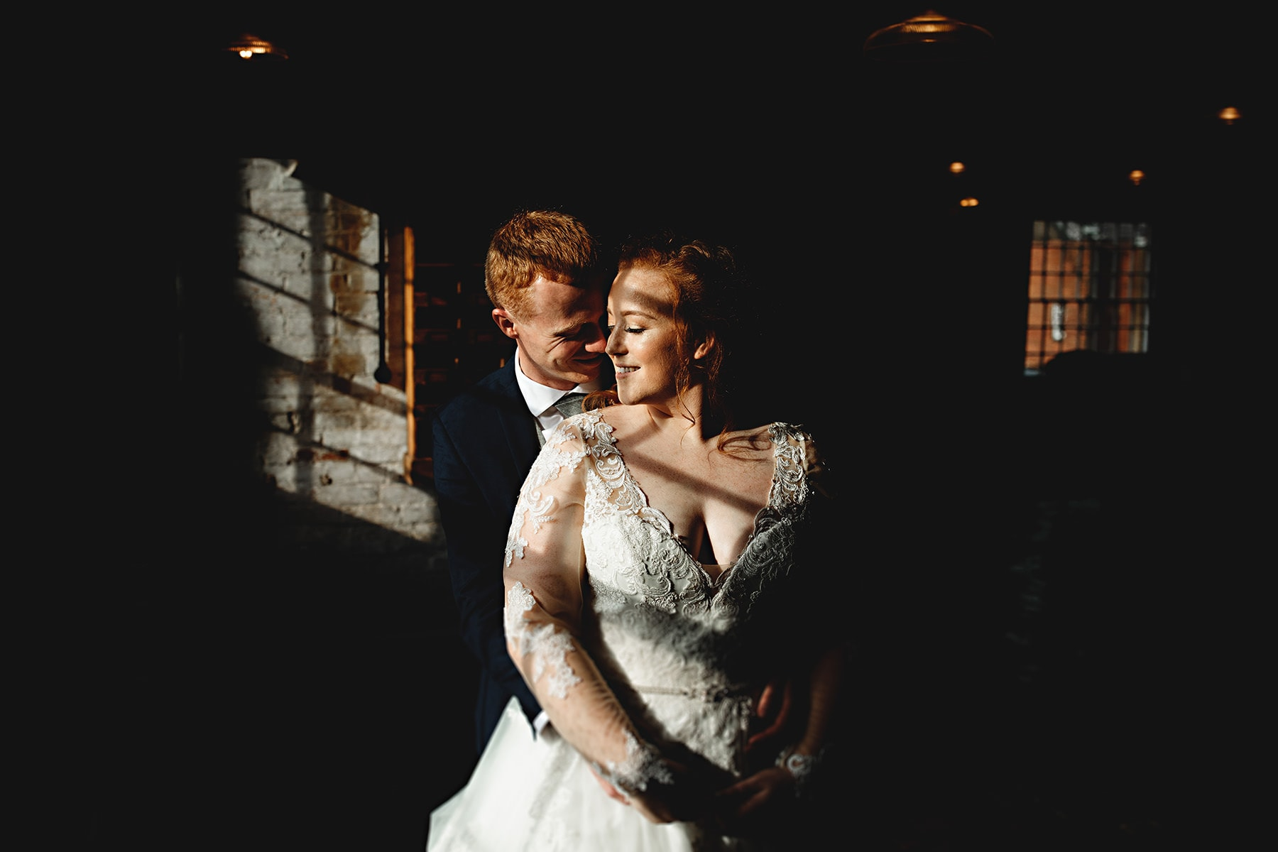 the bride and groom stood in contrasty light at The West Mill in Derbyshire