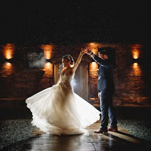 bride and groom dancing in the rain