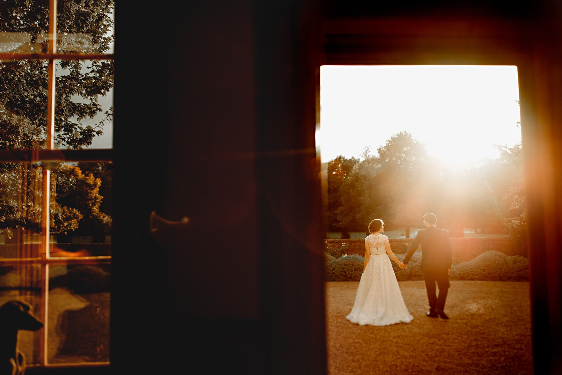 the bride and groom walking off in golden sunshine at the wedding venue