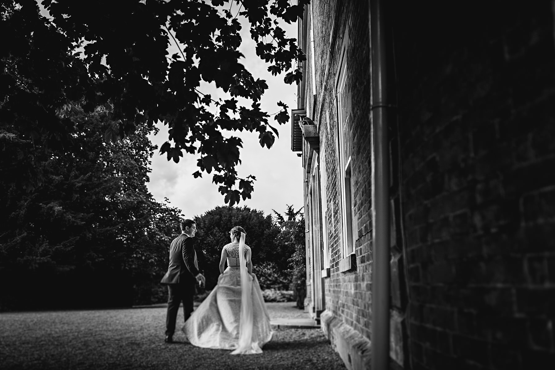 the bride and groom in black and white walking at the wedding venue