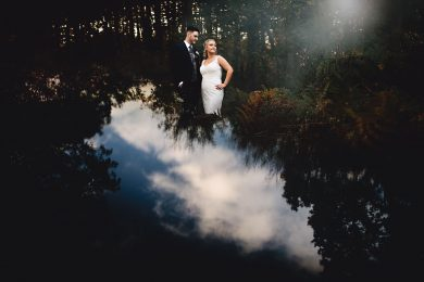 the bride and groom stood in the woodland at Hazel Gap with the blue sky reflected on the ground