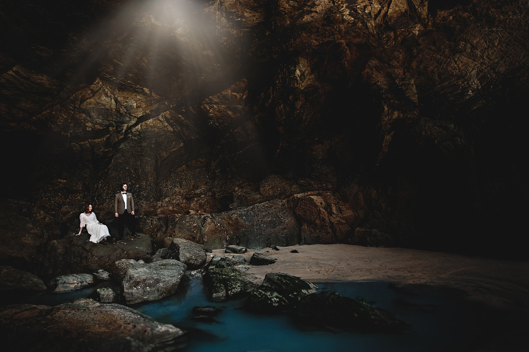 the briade and groom in the caves on lusty beach in cornwall on thier wedding day