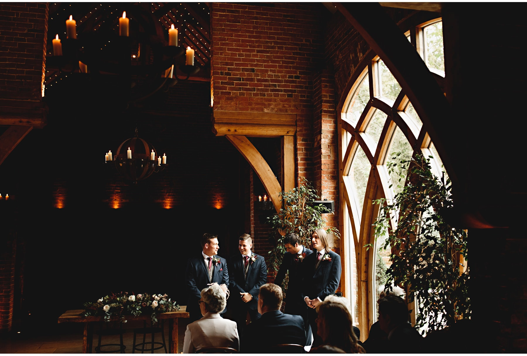 The wedding ceremony, the groom and best man standing in the light.