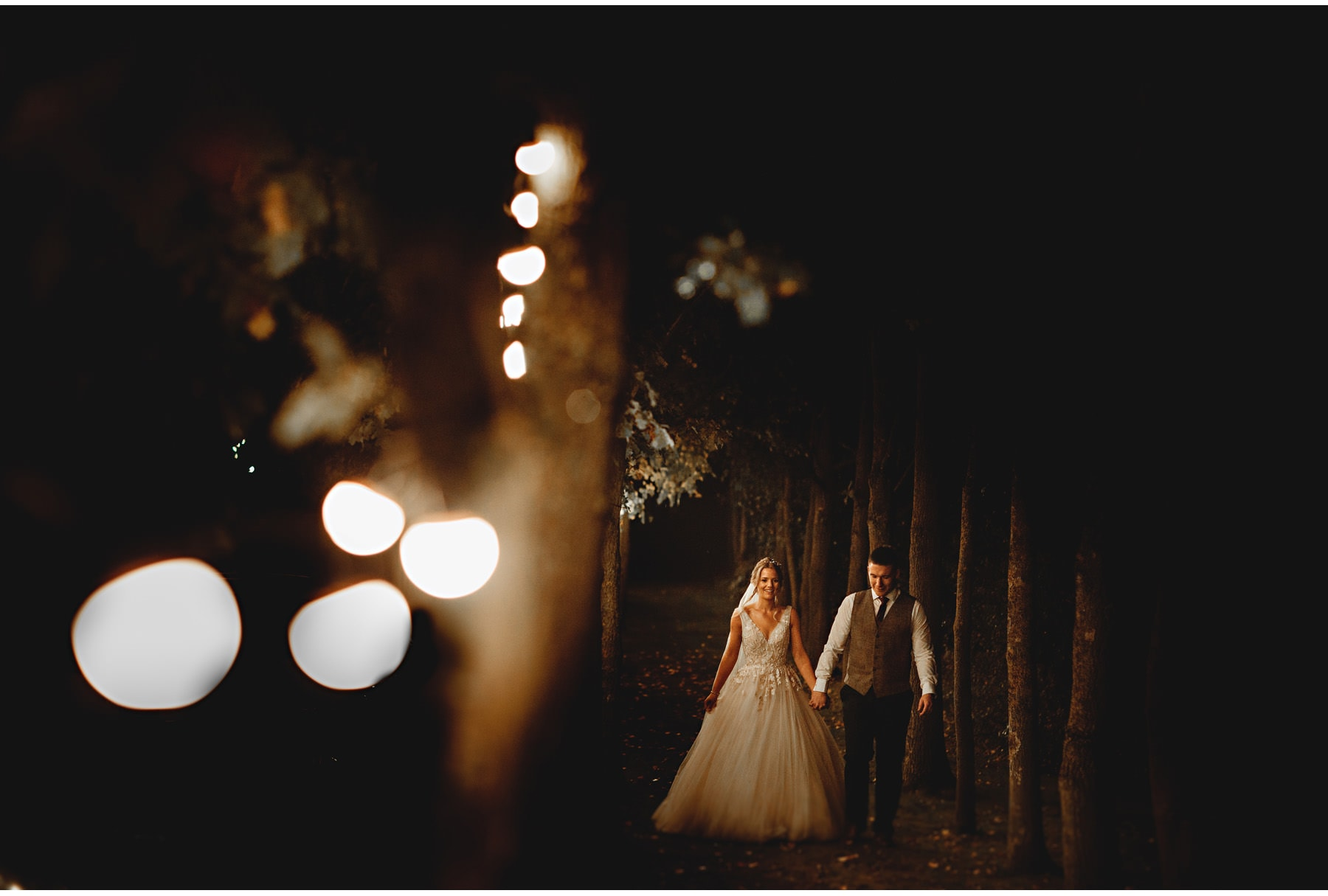 the bride & groom walking by the festoon lights