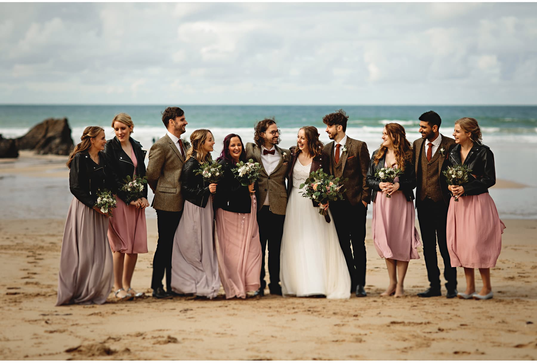 the bride & groom with their bridal party on the beach