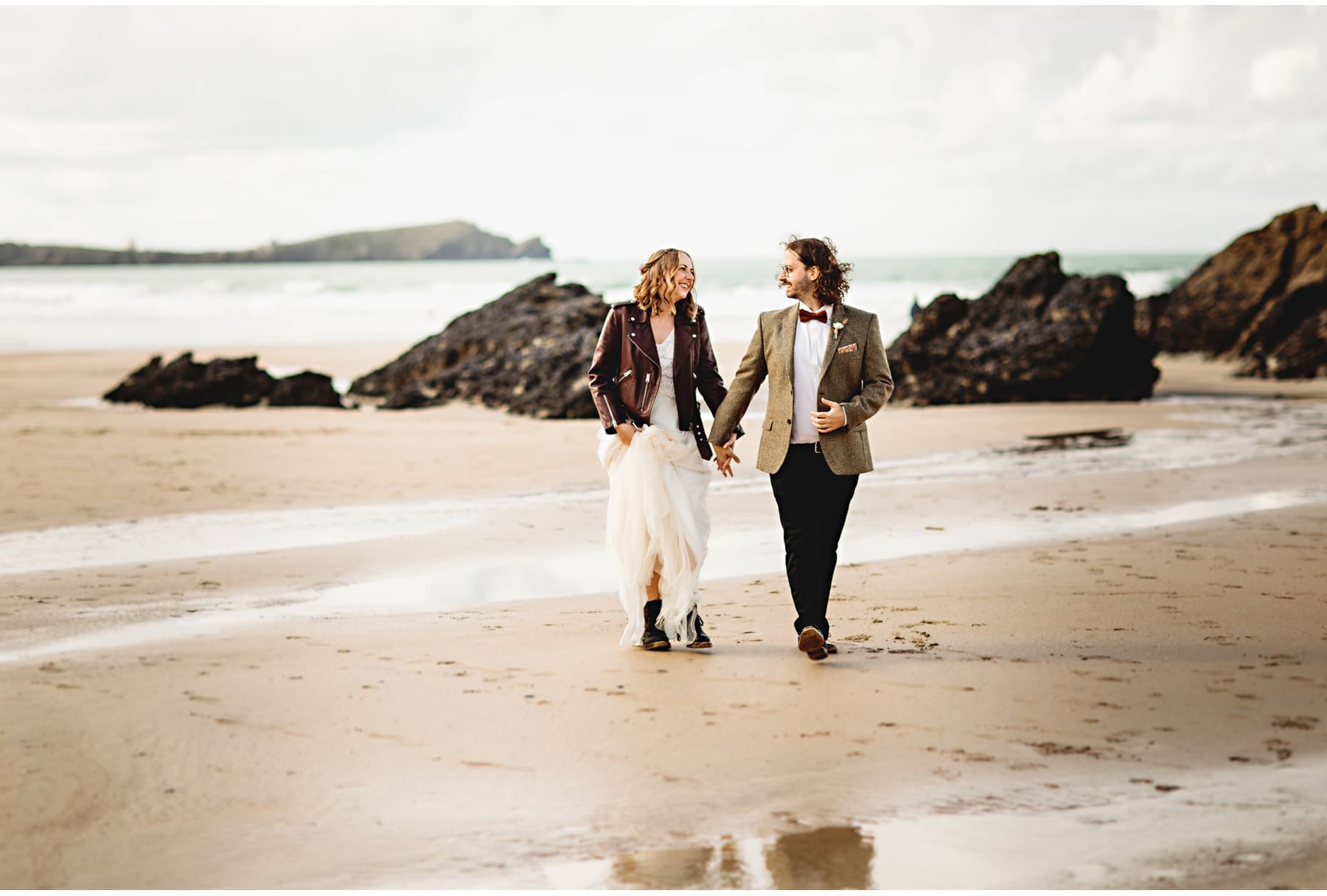 the bride and groom walking on the beach