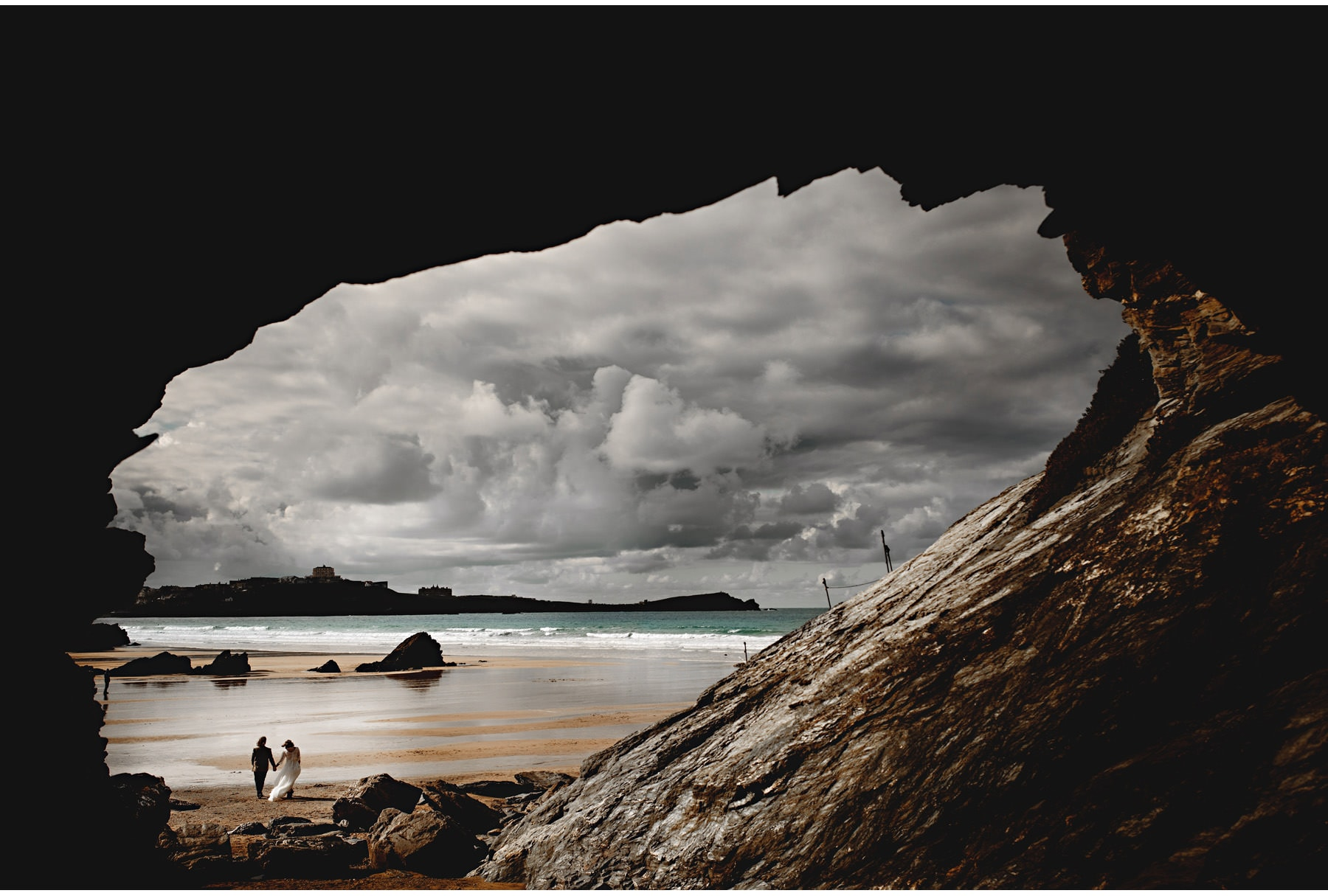 the bride and groom walking on the beach taken from inside a cave