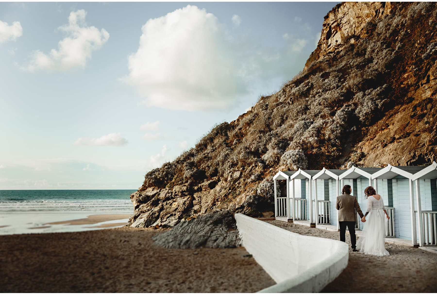 the bride & groom by the beach huts