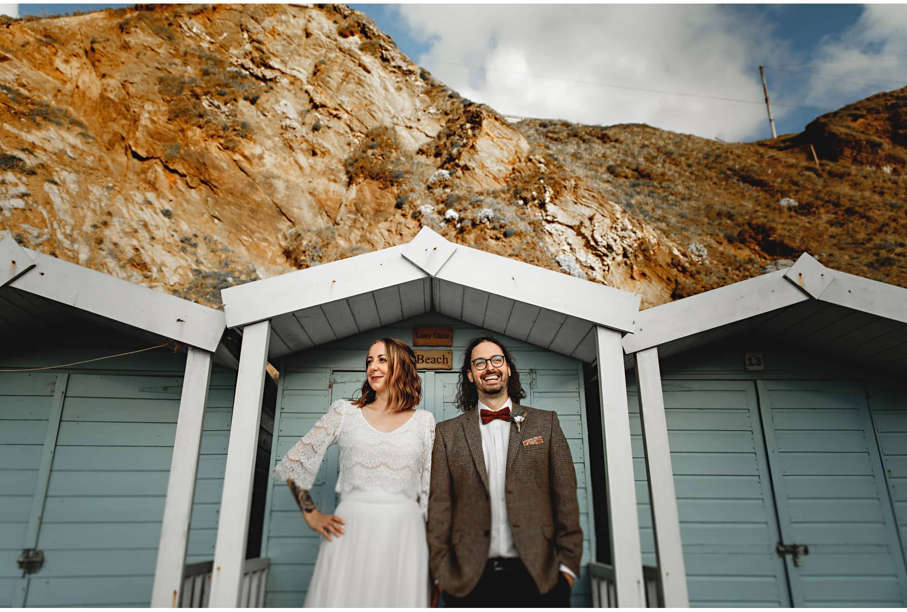 the bride & groom in front of the beach huts