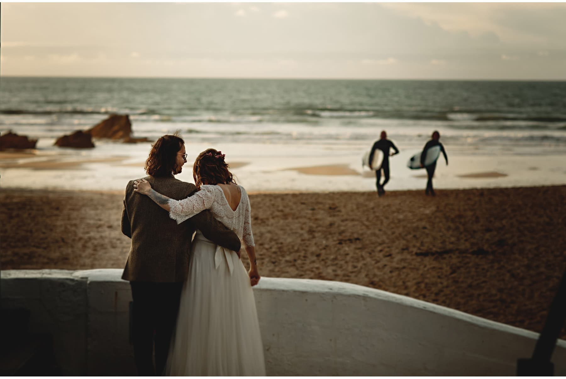 the bride & groom watching surfers on the beach