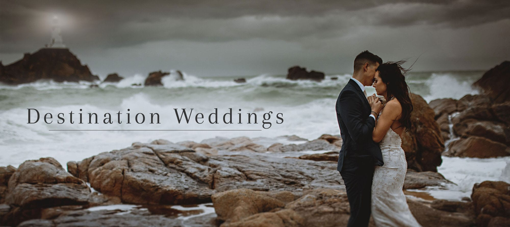 a bride and groom stood on rocks hugging by the storms seas