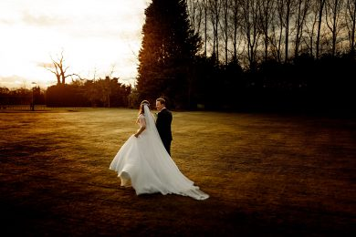the bride and groom walking around the grounds in golden sunlight at wrenbury hall in cheshire on their wedding day
