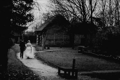 the bride and groom walking around the building of Avoncroft Museum