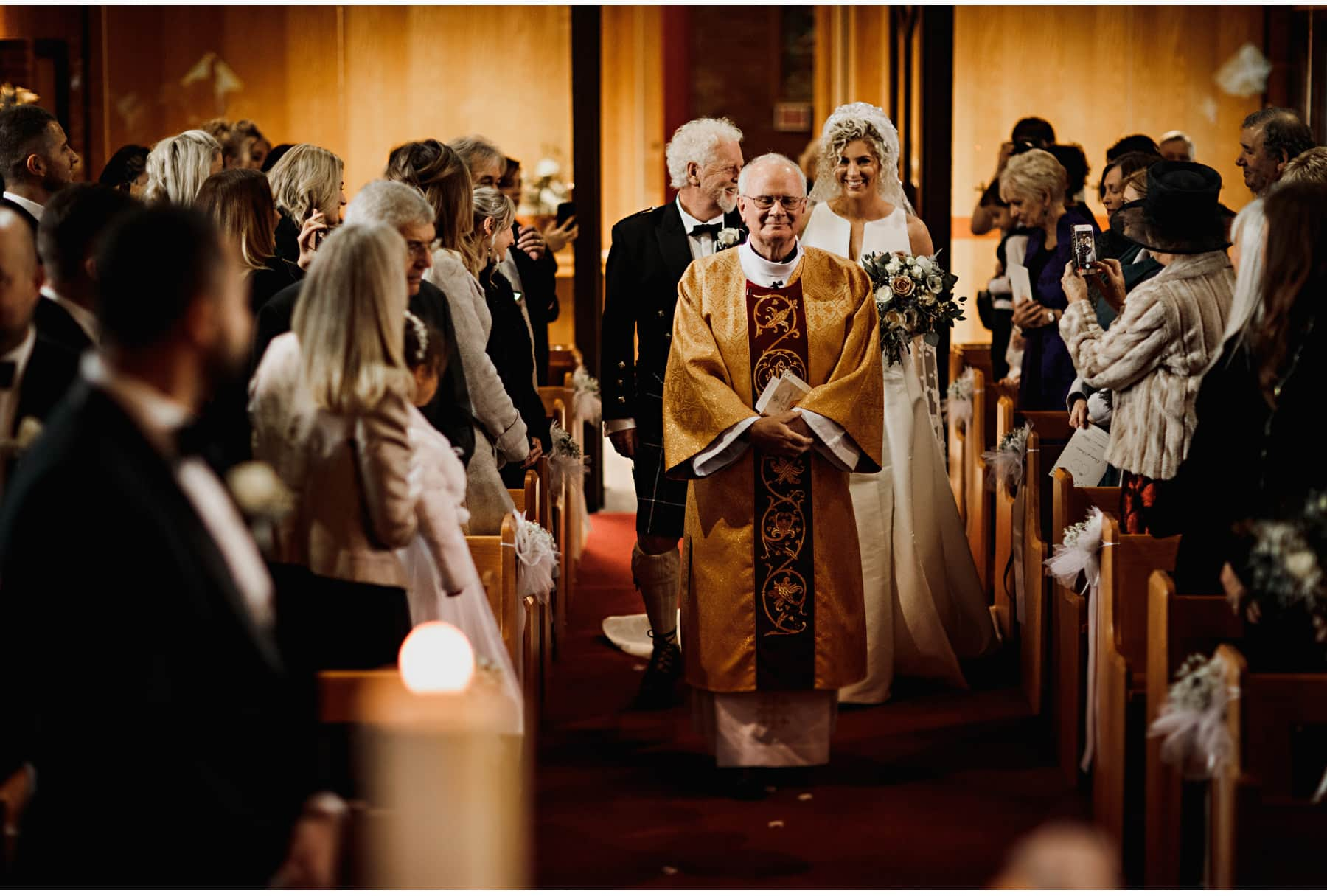 The bride walking into the church with her dad