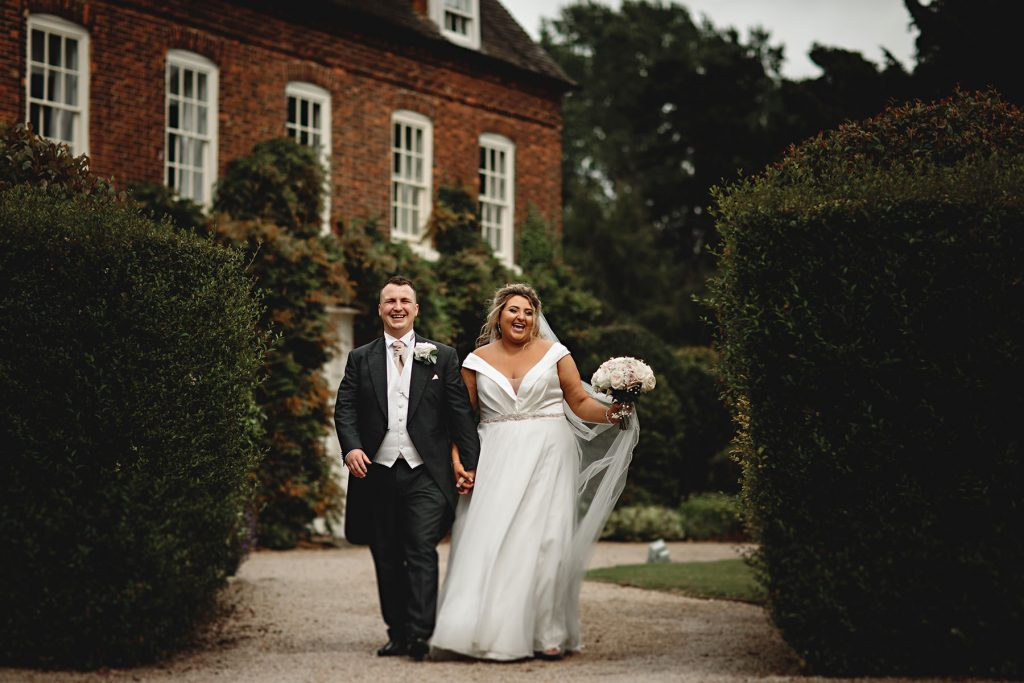 the bride and groom walking away from the stunning alrewas hayes wedding venue on the derbyshire staffordshire border
