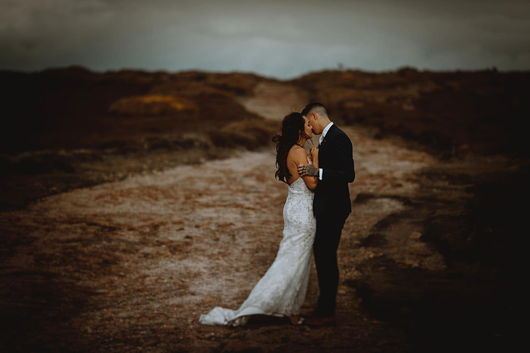 bride and groom stood together in llove in a barren rockey landscape