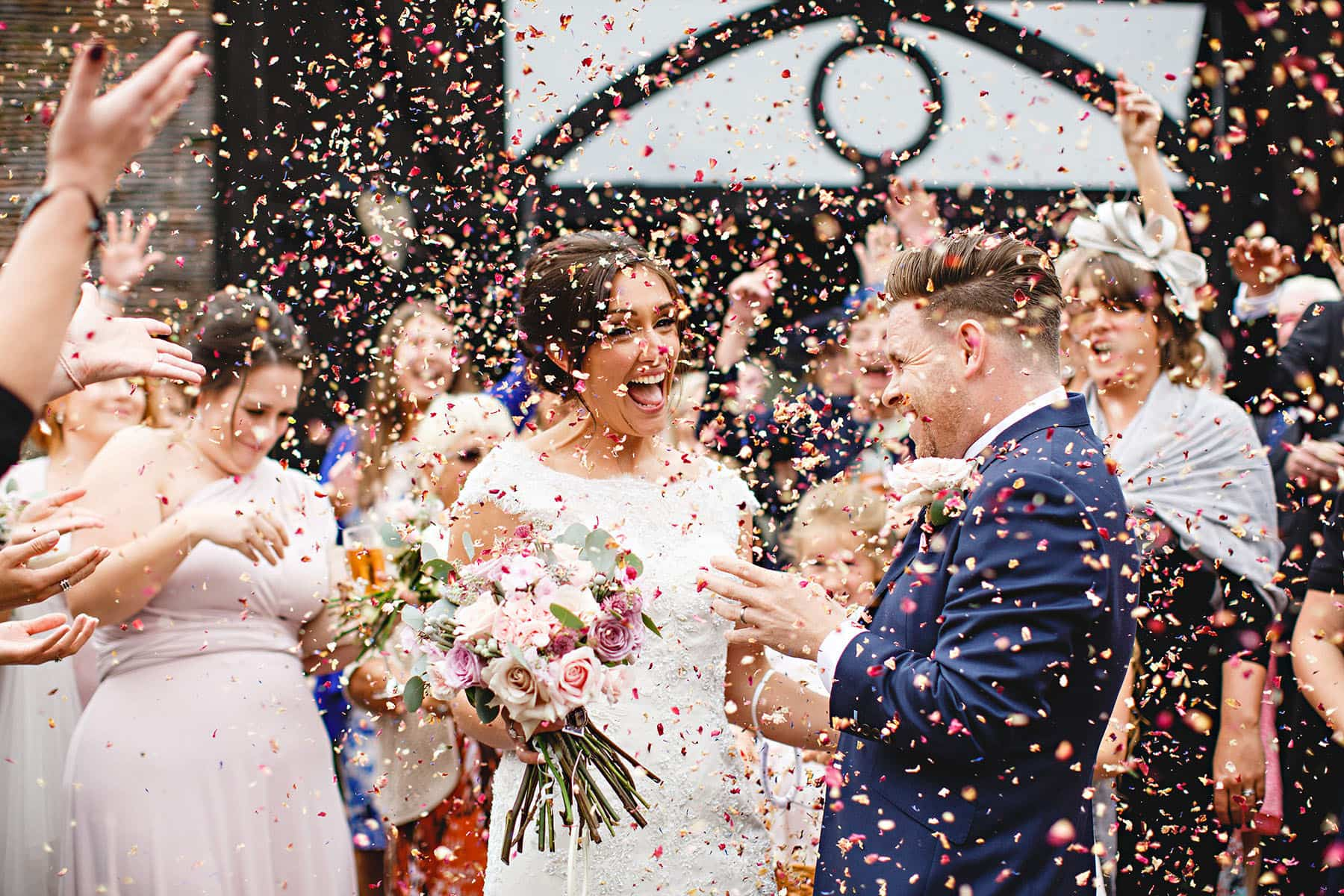 wedding guests throwing cofetti and the bride and groom are happy and excited on their wedding day